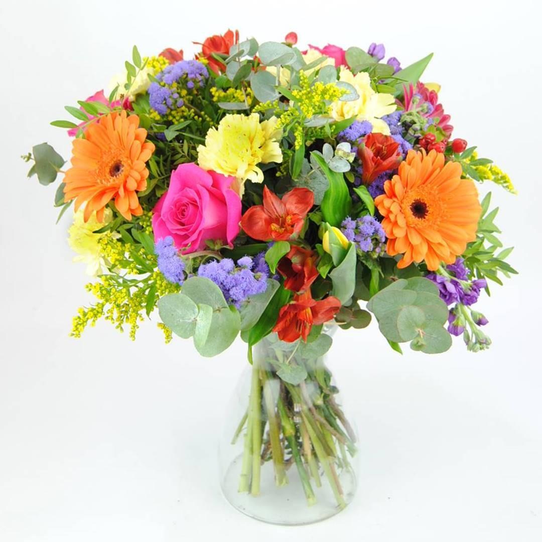 Ramo de flores con Rosa fucsia, Clavel amarillo, Gerbera naranja, Gerbera fucsia, Alstroemeria roja, Solidago, Hipericum rojo, Alelí azul, Tulipán amarillo